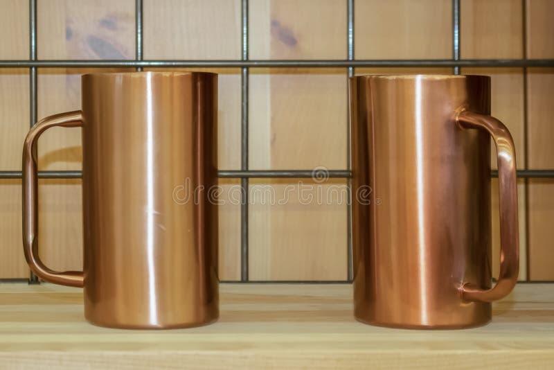 Twee kopermokken zitten op een hout en draadnetplank - selectieve nadruk royalty-vrije stock afbeeldingen