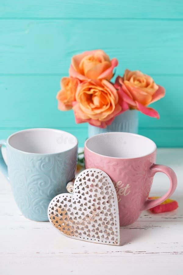 Twee koppen en harten en verse oranje rozen tegen turkoois stock foto's