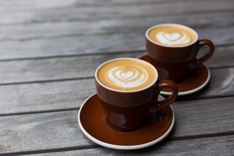 Twee koppen van cappuccino met de latte-kunst van de hartvorm op houten achtergrond royalty-vrije stock fotografie