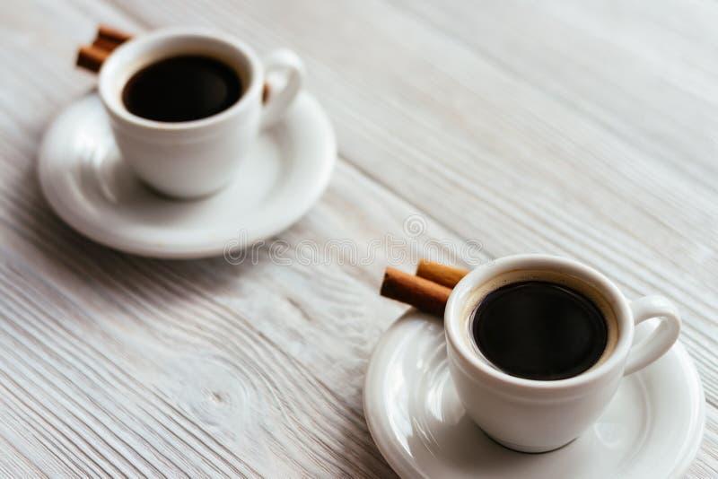 Twee koppen van espresso met pijpjes kaneel op een witte houten lijst royalty-vrije stock fotografie