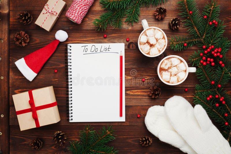 Twee koppen van hete cacao of chocolade met heemst, giften, vuisthandschoenen, Kerstmisspar en notitieboekje met om lijstvlakte t stock afbeelding