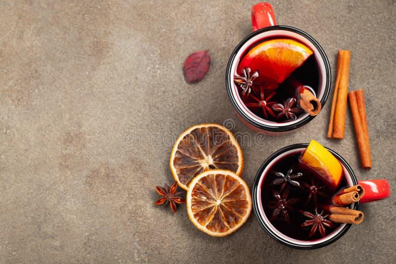 Twee koppen van Kerstmis overwogen wijn of gluhwein met kruiden en oranje plakken op de rustieke mening van de lijstbovenkant Tra stock foto