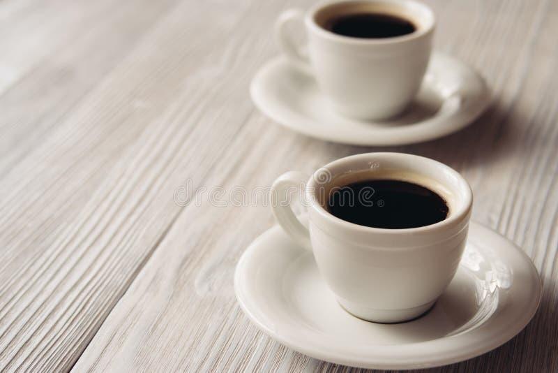 Twee koppen van koffie op een witte houten lijst stock foto