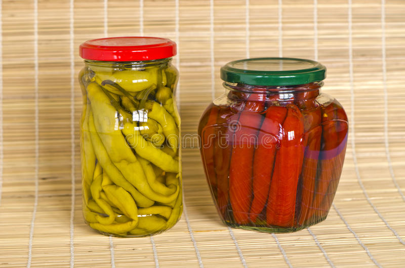 Twee kruiken met gemarineerde pepergroenten stock foto's
