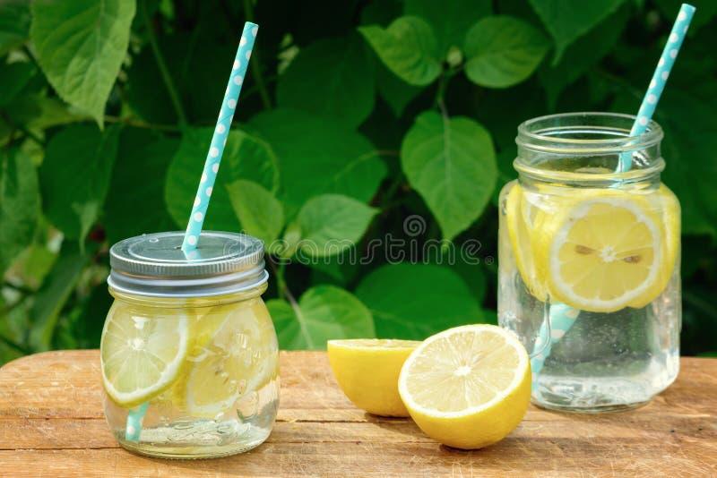 Twee kruiken van limonadetribune op een houten tribune Een achtergrond van een groene struik in een onduidelijk beeld In de kruik stock foto's