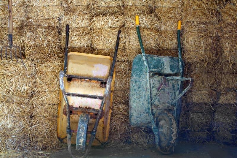 Twee kruiwagens op de hooiachtergrond stock afbeeldingen