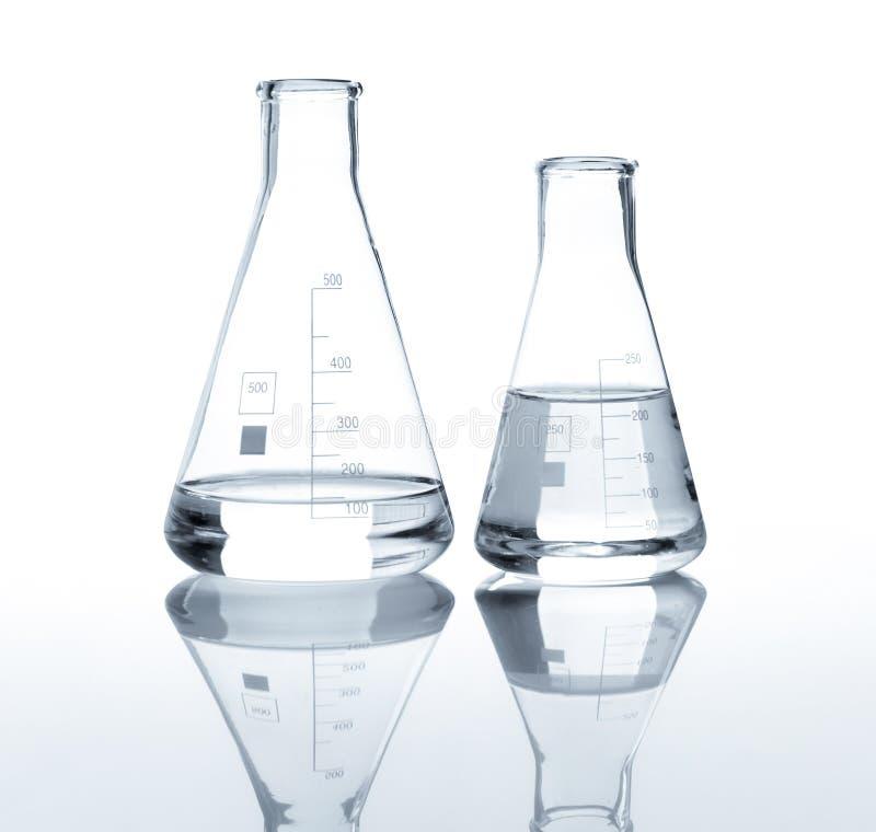 Twee laboratoriumflessen met een duidelijke vloeistof stock foto