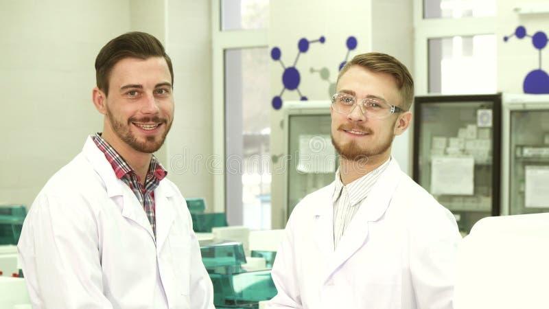 Twee laboratoriumtechnici communiceren over werkende onderwerpen stock afbeelding