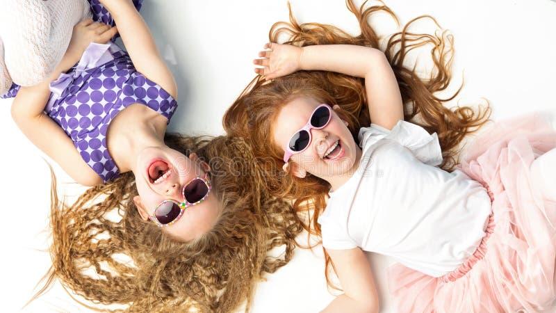 Twee lachende meisjes die op een witte vloer liggen stock afbeeldingen