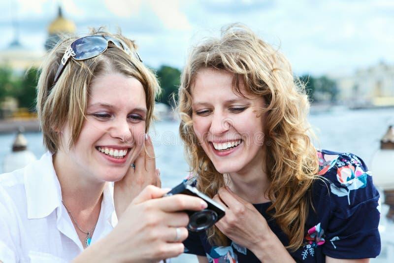 Twee lachende schoonheidsvrouwen die het scherm van camera bekijken royalty-vrije stock foto