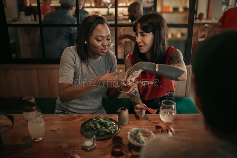 Twee lachende vrienden aan een bistro tafel die eten delen royalty-vrije stock fotografie