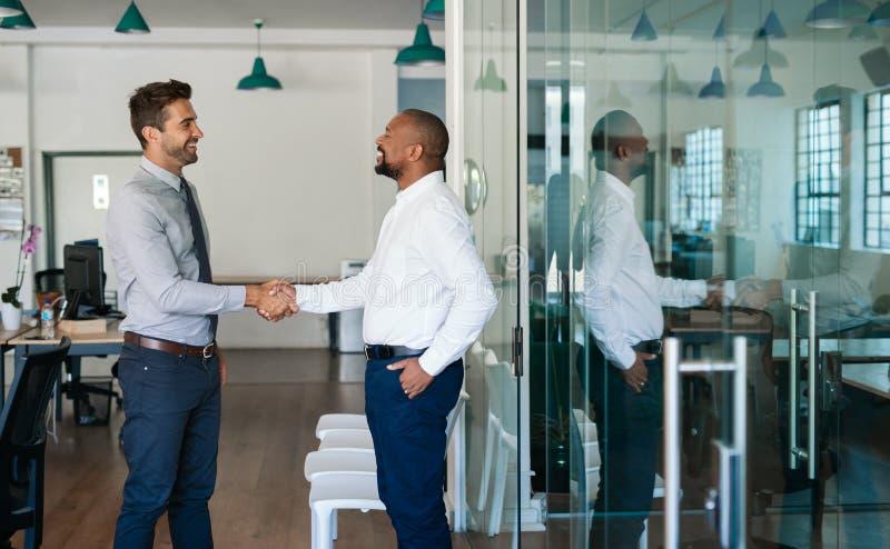 Twee lachende zakenlieden die handen samen na een bureauvergadering schudden stock foto's