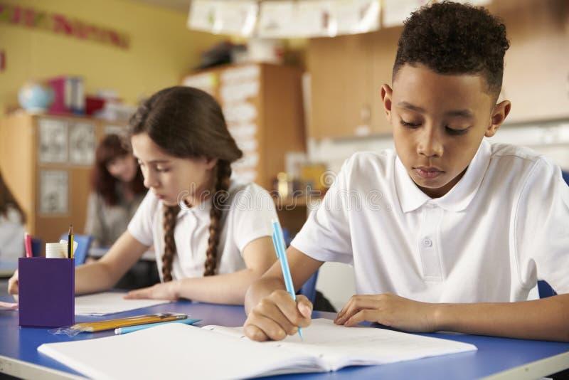 Twee lage schoolleerlingen bij hun bureaus in klasse, sluiten omhoog stock afbeelding