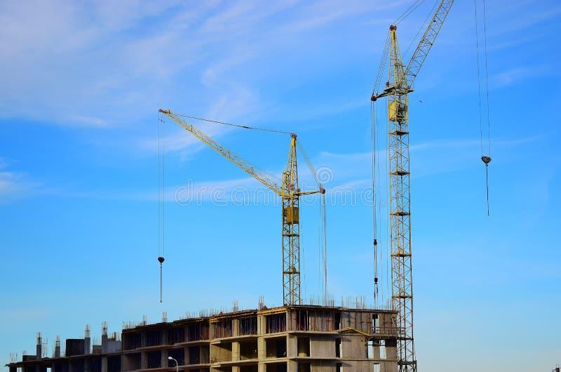 Twee lange kraantribune dichtbij een huis in aanbouw op blauwe hemelachtergrond royalty-vrije stock foto