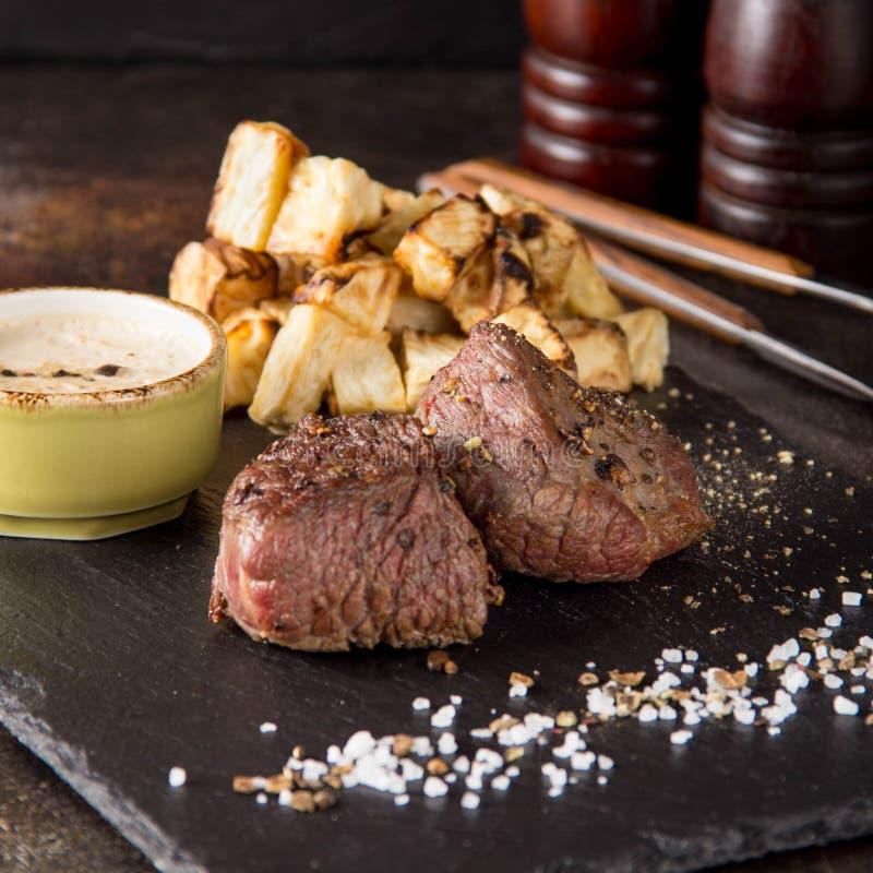 Twee lapje vleesfilethaakwerk Mignon met bijgerecht van aardappelen in de schil en selderie, met zout en peper Het mooie restaura royalty-vrije stock fotografie