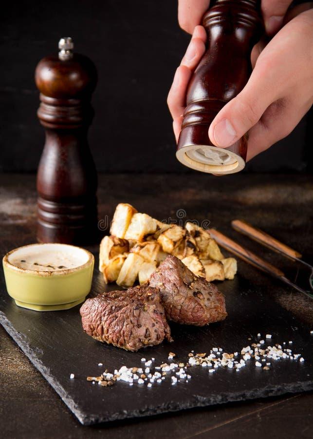 Twee lapje vleesfilethaakwerk Mignon met bijgerecht van aardappelen in de schil en selderie, met zout en peper Het mooie restaura stock afbeeldingen