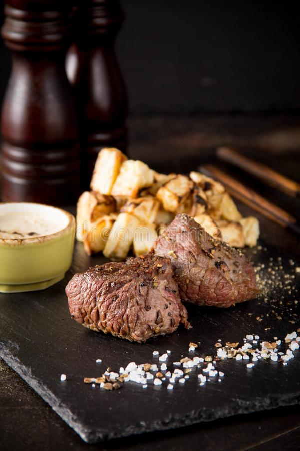 Twee lapje vleesfilethaakwerk Mignon met bijgerecht van aardappelen in de schil en selderie, met zout en peper Het mooie restaura stock foto's