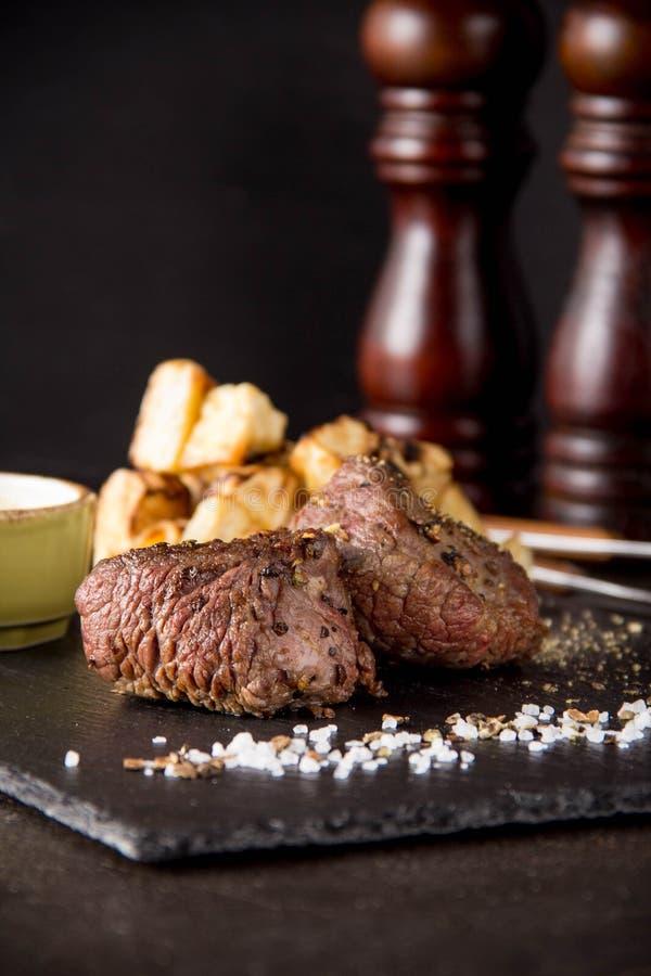Twee lapje vleesfilethaakwerk Mignon met bijgerecht van aardappelen in de schil en selderie, met zout en peper Het mooie restaura stock fotografie