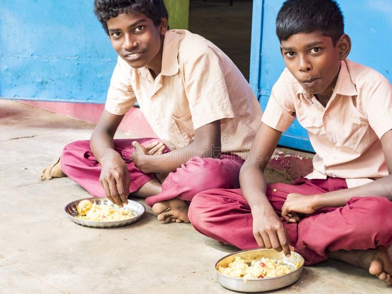 Twee leerlingen die van Jongenstieners gediende Maaltijdplaat van rijst in de Kantine van de overheidsschool zijn Ongezond voedse stock fotografie
