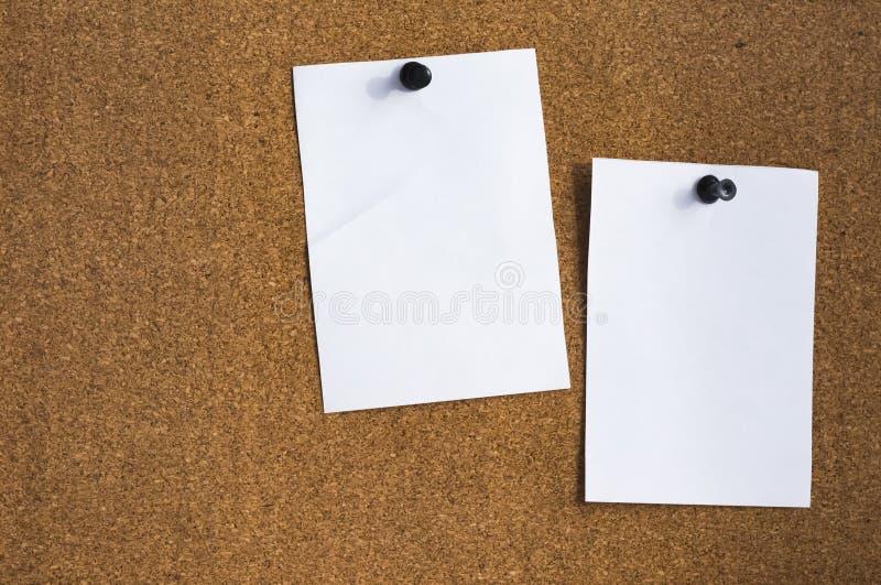Twee lege bladen van document in bijlage aan de cork Raad met een drukknop royalty-vrije stock afbeeldingen
