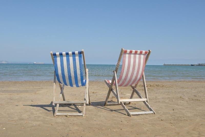 Twee lege blauwe linnenligstoelen één en één rood in het midden van het beeld op het strand, facin royalty-vrije stock foto