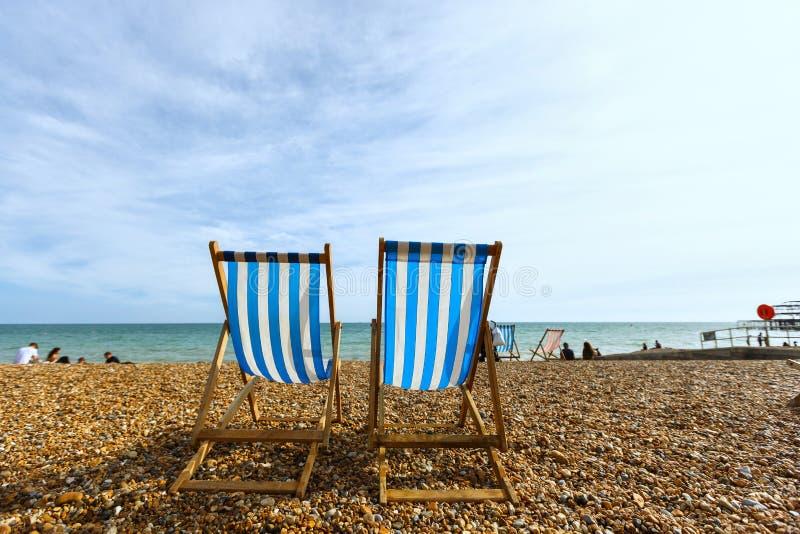Twee lege gestreepte vouwende ligstoelen op zeekust in Brighton, onbekende mensen stock fotografie
