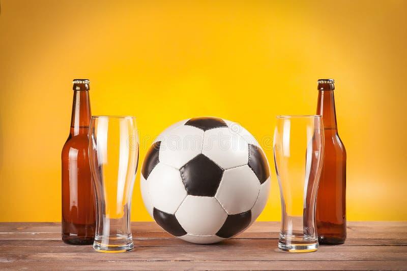Twee lege glazen bier en flessen dichtbij voetbalbal stock afbeeldingen