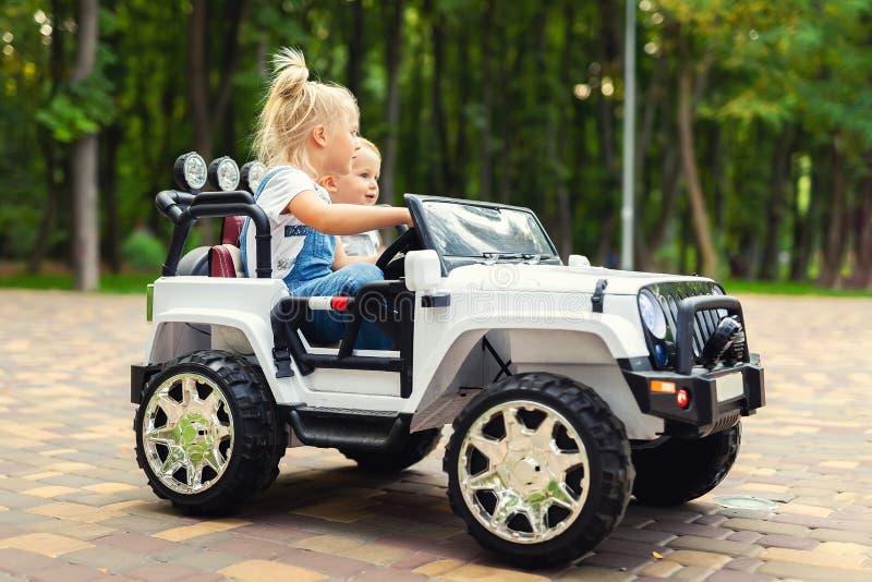 Twee leuke aanbiddelijke blonde sibingskinderen die pret hebben die elektrische stuk speelgoed suv auto in stadspark berijden De  stock foto's
