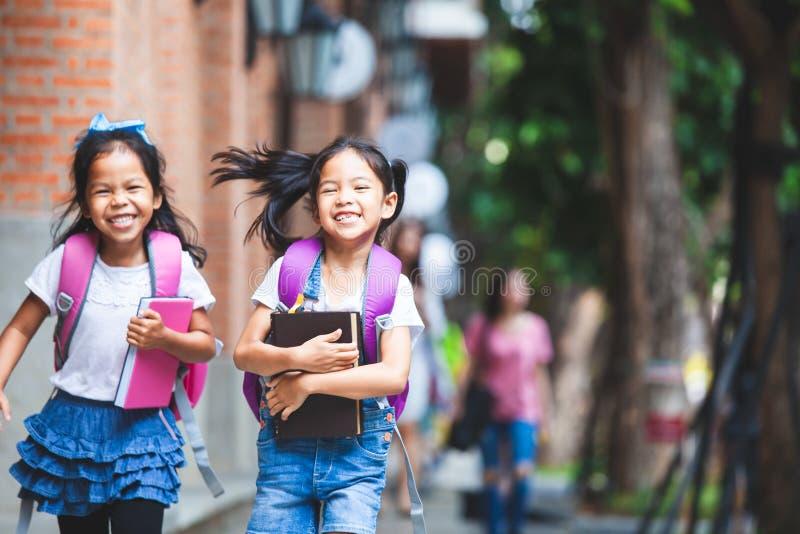 Twee leuke Aziatische kindmeisjes met schooltasholding boeken en lopen samen in de school royalty-vrije stock afbeeldingen