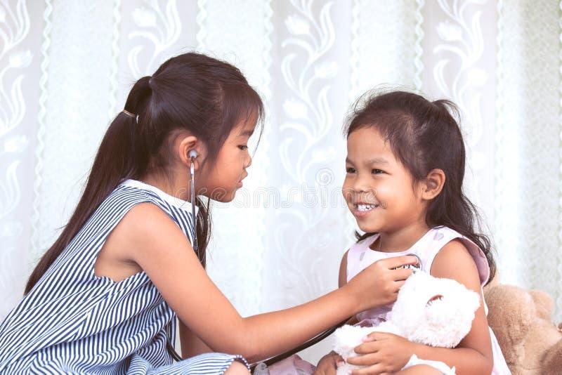 Twee leuke Aziatische kleine kindmeisjes die arts en patiënt spelen royalty-vrije stock afbeelding