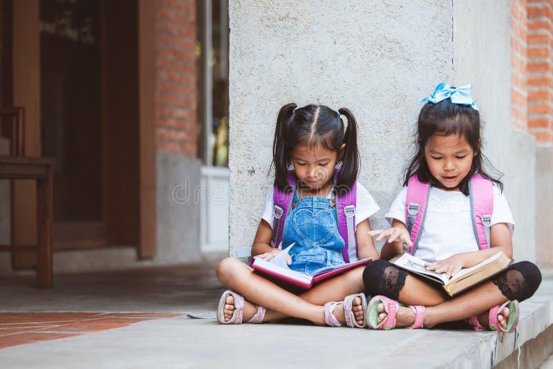 Twee leuke Aziatische leerlingsmeisjes die een boek samen in de school met pret en geluk lezen stock afbeelding