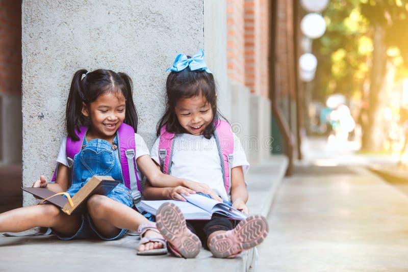 Twee leuke Aziatische leerlingsmeisjes die een boek samen in de school met pret en geluk lezen stock foto's