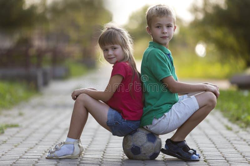 Twee leuke blonde gelukkige jonge kinderen, glimlachende jongen en langharige meisjeszitting rijtjes op voetbalbal op lege zonnig royalty-vrije stock afbeelding