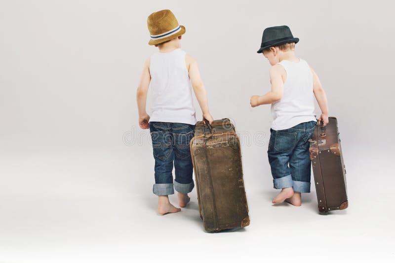 Twee leuke broers die met hun koffers weggaan stock afbeeldingen