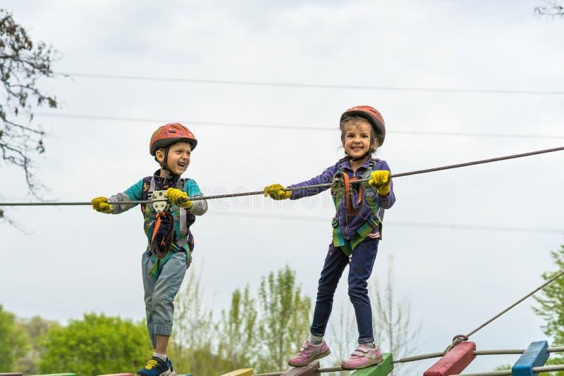 Twee leuke gelukkige jonge kinderen, jongen en meisje in beschermende uitrusting, karabijn en veiligheidshelmen op kabelmanier op stock foto