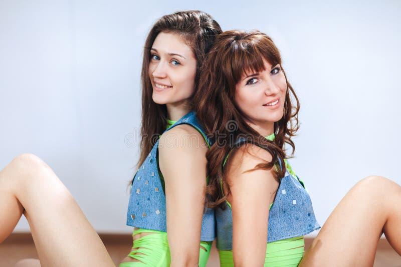 Twee leuke glimlachende donkerbruine meisjes of vrouwen in denimvest zitten rijtjes, bekijkend de camera, close-up royalty-vrije stock foto's