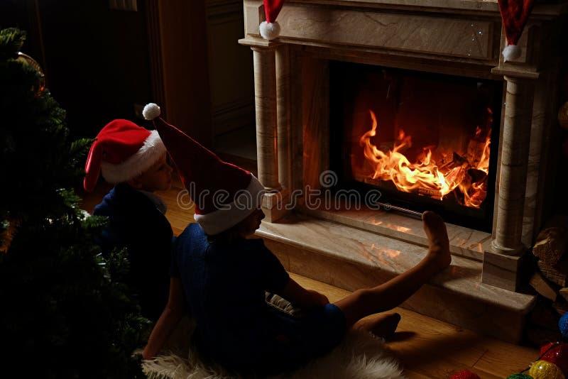Twee leuke jonge geitjes die dichtbij de open haard in Kerstmis verfraaide ruimte zitten royalty-vrije stock foto