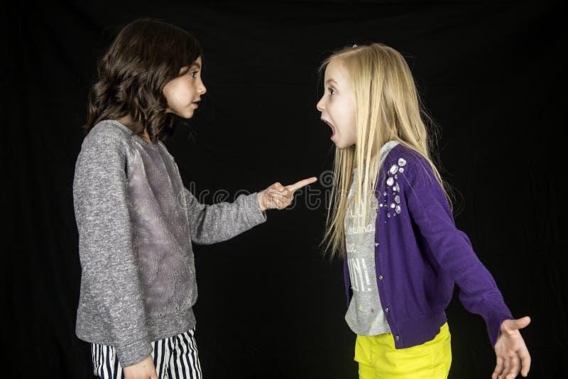 Twee leuke jonge meisjes die één meisje stellen die vinger richten royalty-vrije stock fotografie