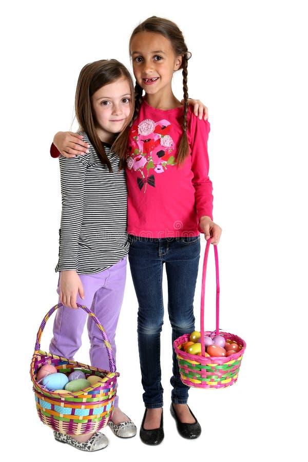 Twee leuke jonge meisjes die de manden van holdingspasen koesteren stock foto