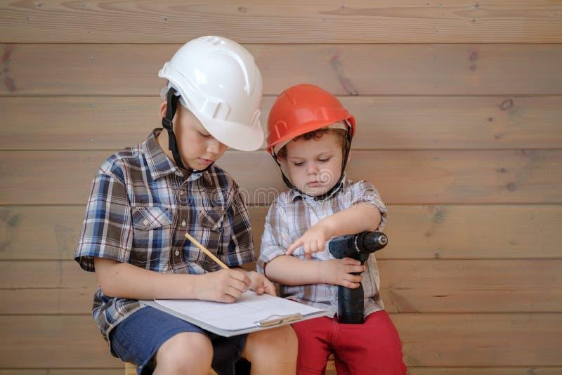 Twee leuke jongens in bouwhelmen bespreken een plan voor het aanstaande werk De kinderen spelen bouwers royalty-vrije stock foto's