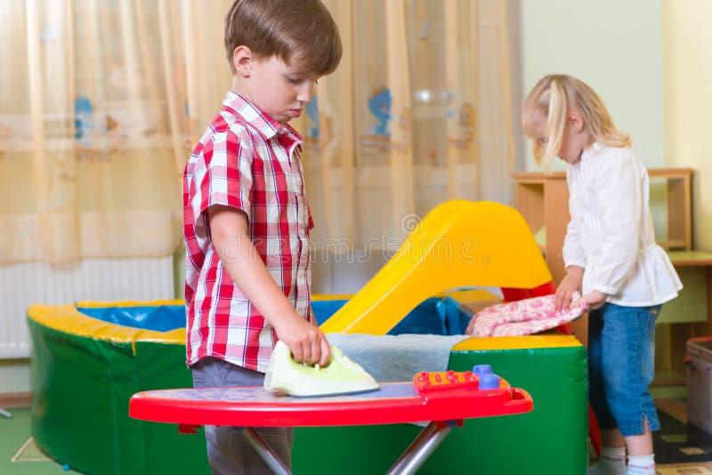 Twee leuke kinderen die thuis spelen royalty-vrije stock afbeelding