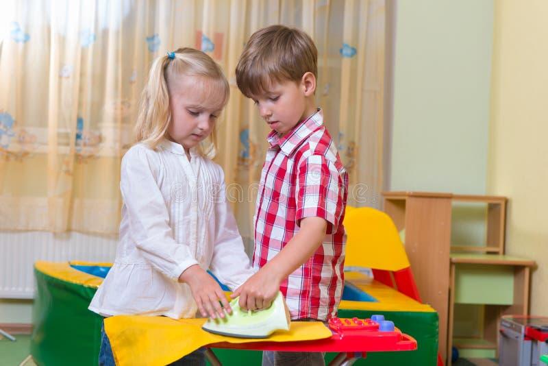 Twee leuke kinderen die thuis spelen royalty-vrije stock afbeeldingen