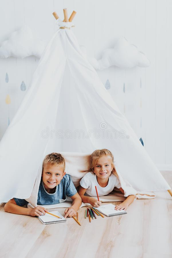 Twee leuke kinderen die zich in wigwam samentrekken stock afbeelding