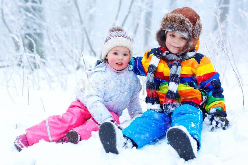 Twee leuke kleine jonge geitjesjongen en meisje in de winter sneeuwbos bij sneeuwvlokkenachtergrond in openlucht vrije tijd en le stock fotografie