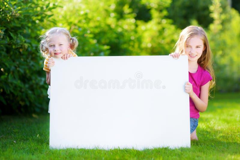 Twee leuke kleine zusters die grote spatie houden whiteboard stock afbeeldingen
