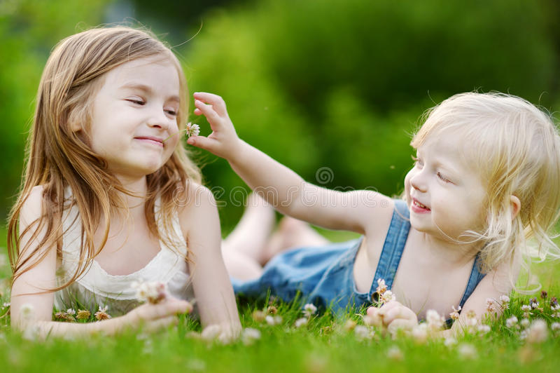 Twee leuke kleine zusters die in het gras leggen royalty-vrije stock foto
