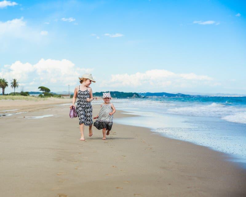 Twee leuke kleine zusters die pret op een strand hebben stock foto