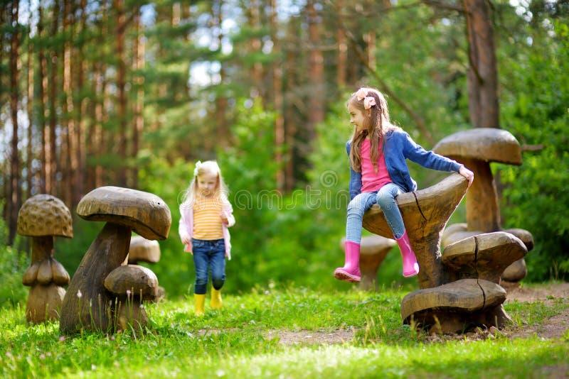 Twee leuke kleine zusters die pret op reuze houten paddestoelen hebben royalty-vrije stock foto's