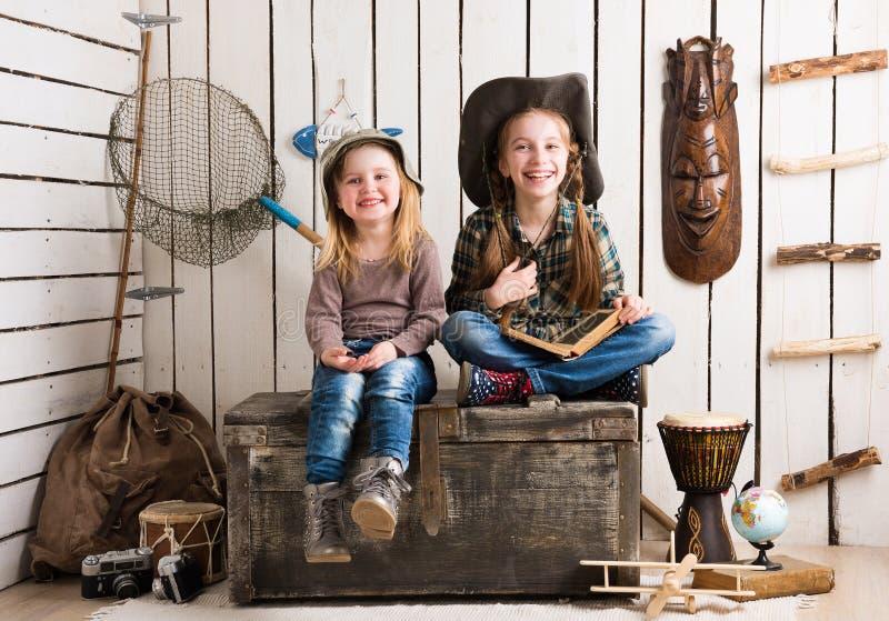 Twee leuke meisjes die op grote houten borst zitten royalty-vrije stock fotografie