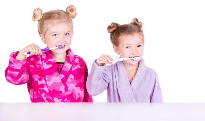 Twee leuke meisjes die tanden borstelen stock afbeelding